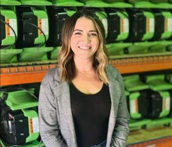 Female standing in front of green air movers