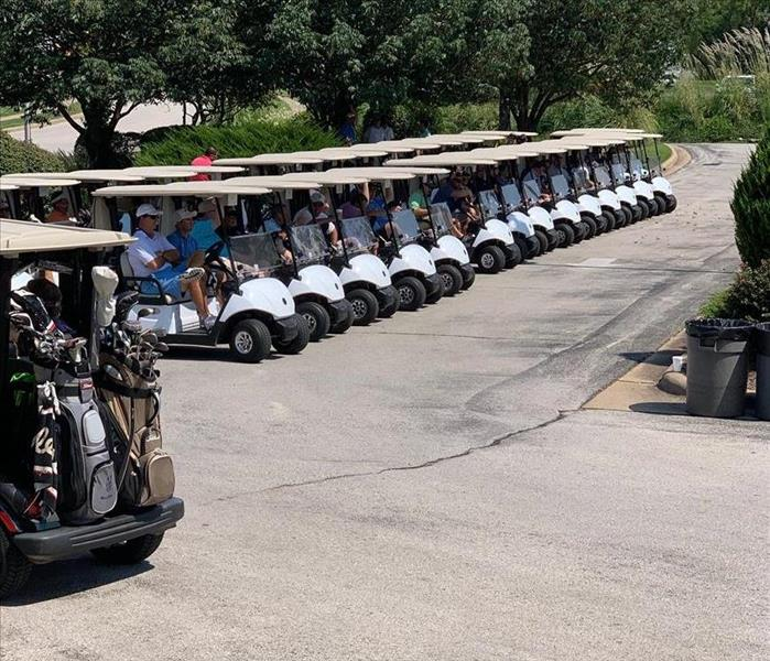 Golfers sitting in golf carts lined up and ready to golf at the tournament