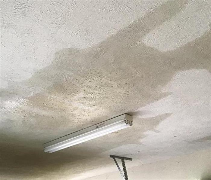 storm damaged ceiling with water spots